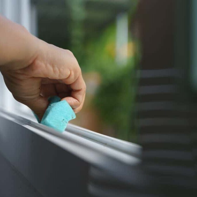 Hand holding sponge for cleaning dust on the glass window rail
