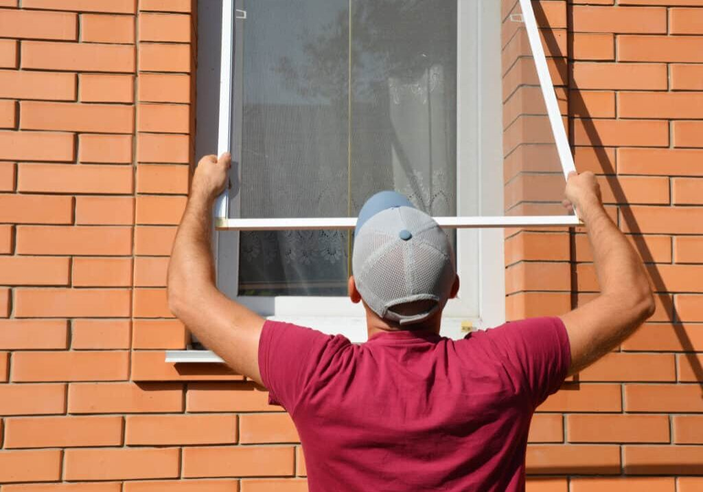 Contractor installing mosquito wire screen on house window to protect from insects. Mosquito wire screen installation.